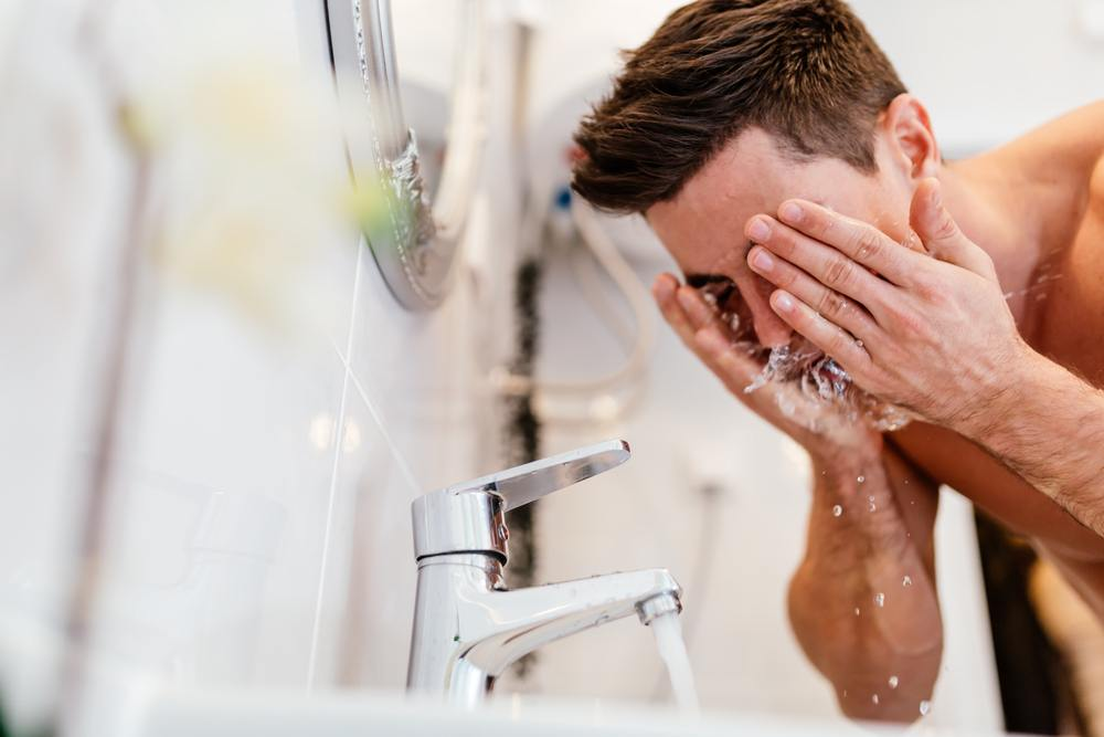 man washes his face in sink