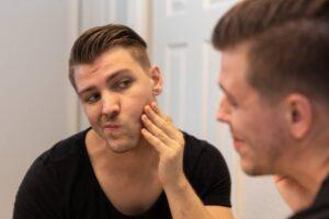 Man Examines Skin In Mirror