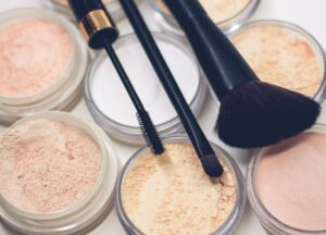 Makeup Powders, Brushes And Mascara Wand On Table
