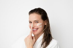 Woman In Robe Applies Moisturizer To Face