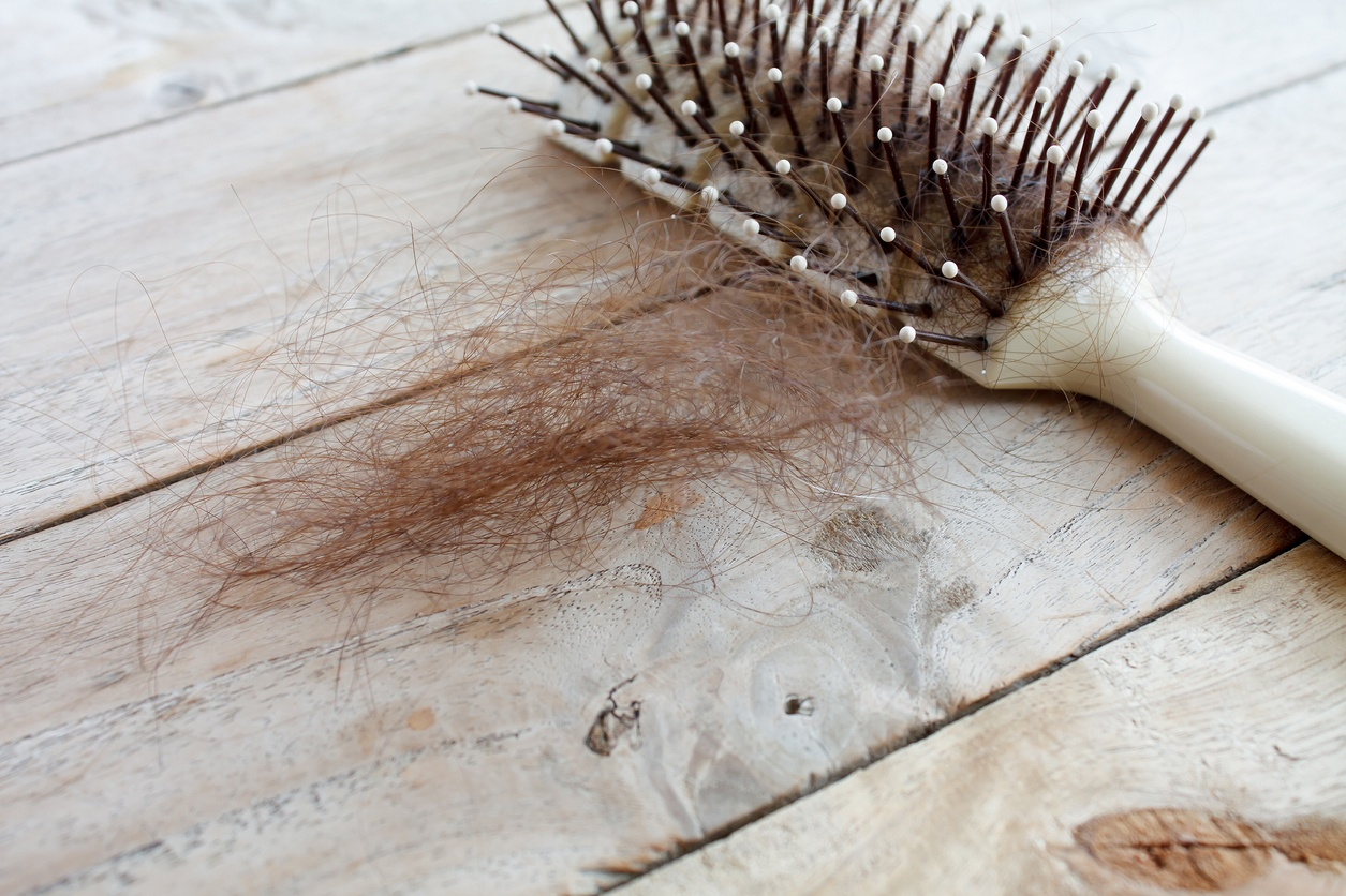 Hairbrush with lots of hair laying on the table