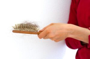 Woman Holding Out Brush With A Lot Of Hair On It